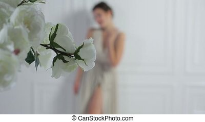 Girl in dress on a background of white flowers