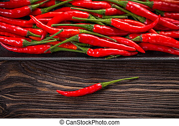 Red hot chili peppers on wooden dark background
