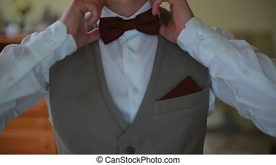 Man in the white shirt correcting bow-tie