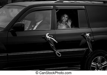 Gorgeous smiling elegant bride in luxury wedding car b&w