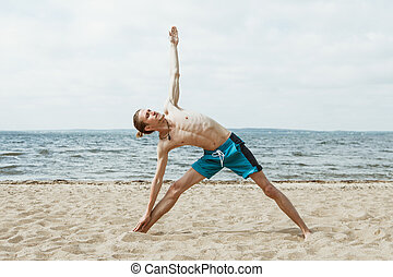 Adult man doing yoga on the beach
