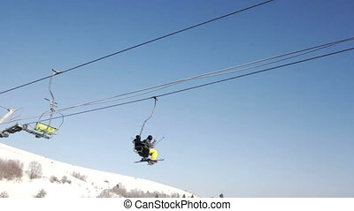 Two skiers riding up ski lift in the mountains