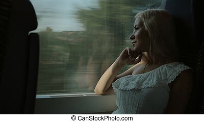Pretty blonde looks through the window of the moving train -...