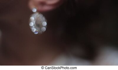 Girl corrects earring with diamond