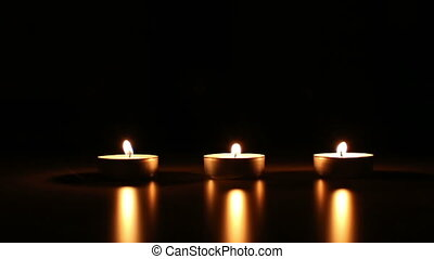 three small candles with wind