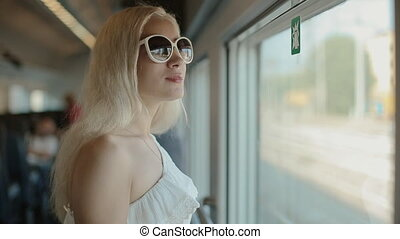 Woman in sunglasses admiring the view from the window in...