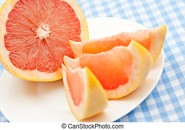 Three pink grapefruit segments on a wooden tray