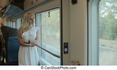 Blue-eyed blonde standing by the window of the train -...