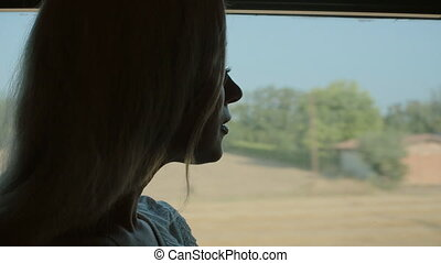 Beautiful girl standing by the window of the train