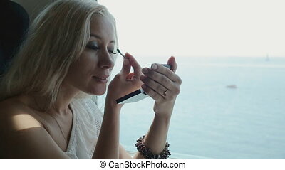 Beautiful blonde applying eye shadow and lip gloss sitting...