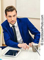 handsome businessman - Handsome businessman sitting at his...