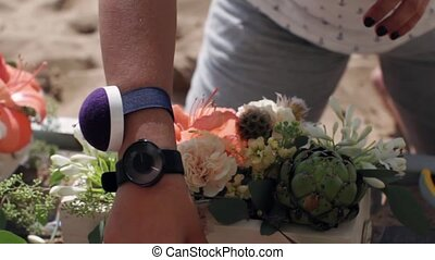 Woman hands decorate wooden flowerbed with different flowers...