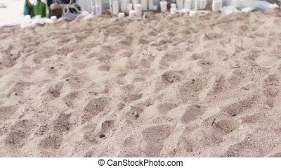 Decorated white table on sand beach in front of sea. Candles, bottles flower