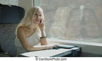 Woman talking on cell phone in the train - Woman talking on...