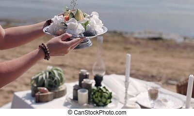 Woman's hands stand flowered dish on table decorated with  candles, sea shells.
