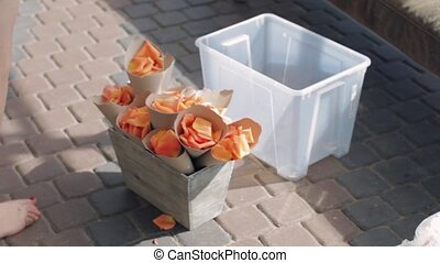 Woman hands decorate wooden flowerbed by tubules with orange petals. Summer