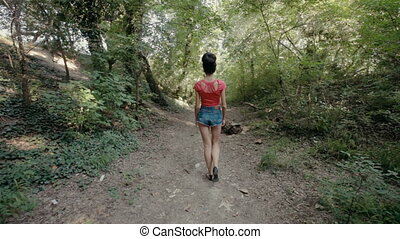 Sexy young woman walking on a path in the woods - Sexy young...