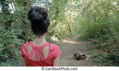 Sexy young woman walking on a path in the woods