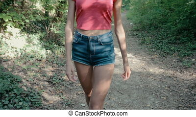 Attractive girl in short shorts walking along a footpath -...