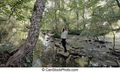 Cute girl standing on a rock in the middle of the river