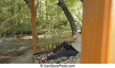 Young woman lying on a carpet in the gazebo in the woods -...