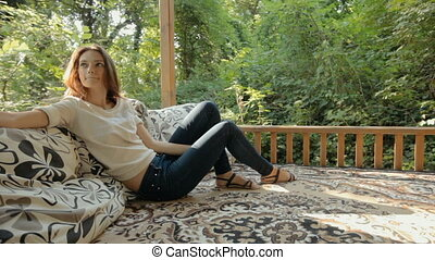 Attractive woman relaxing and sitting on pillows in the...