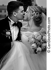 B&W handsome groom in suit with boutonniere kissing beautiful bride with bouquet