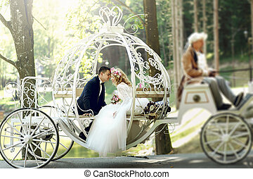 Handsome groom kissing blonde beautiful bride in magical...