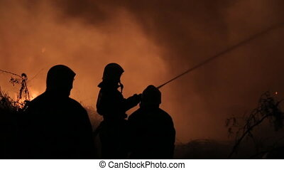 Silhouettes of firefighters extinguish fire at night