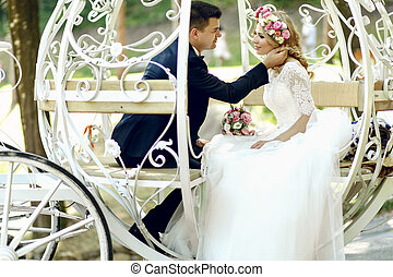 Handsome groom touching blonde beautiful bride in magical...
