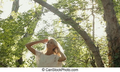 Smiling blond clothed in a dress resting in the forest -...