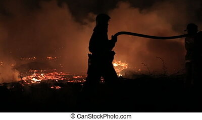 Silhouette rescuers extinguishing fire at night - Silhouette...