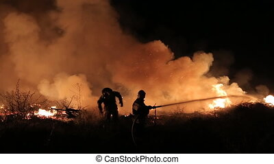 Team of rescuers extinguishing fire at night with water from...