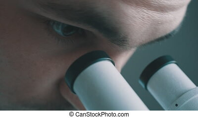 Young doctor  looking through the microscope