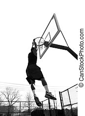 Basketball Slam Dunk - A basketball player hanging from the...