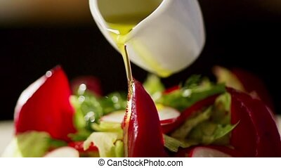 Vegetable salad and olive oil in slow motion - Olive oil in...