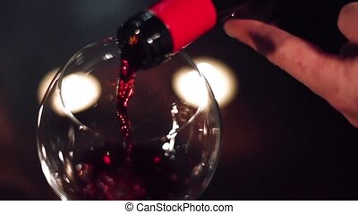 Wine flows in a glass on an evening date in slow motion