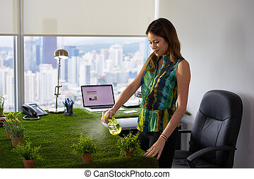Ecologist Business Woman Watering Plants In Corporate Office...