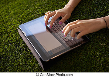 Woman Emailing And Texting With Tablet Computer On Grass