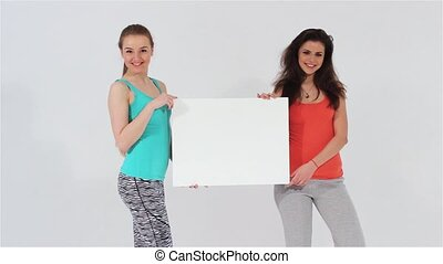 Two sports girl holding white sheet