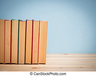 Books on a wooden shelf on a blue background