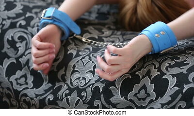 female hands in leather handcuffs sex toys grabs the blanket...
