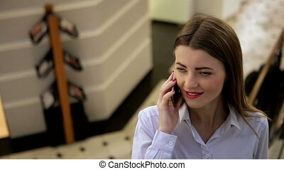 Amazing girl with red lips and red nail polish is talking on her cell phone in a mall