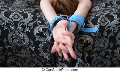 female hands in leather handcuffs sex toys blue skin