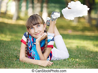 Little girl resting on meadow and daydreaming