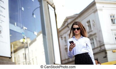 Happy smart businesswoman is walking on the street and make pictures by her cell phone