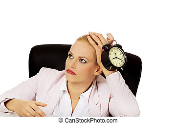 Tired business woman sitting behind the desk and holding...