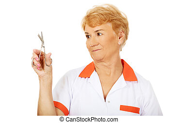 Smile elderly female doctor or nurse holding scissors.