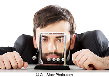 Man moving newton balls in office - Businessman moving...