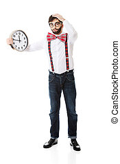 Man wearing suspenders holding big clock - Worried man...